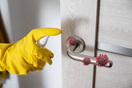 Coronavirus, covid 19 protection. Hand disinfects and cleans door handle with antibacterial wet wipes to protect against viruses, germs and bacteria during coronavirus