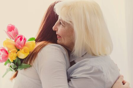 Mom and daughter are hugging. Mohm day concept. Adult european blonde woman holding a bouquet of tulips flowers. Mothers Day.