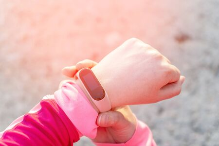 Close up of sporty woman using a fitness tracker on the street. Preparation for marathon, healthy lifestyle Stock Photo