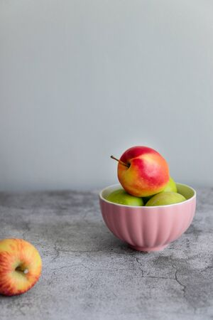 Green red organic healthy apples in pink bowl on grey board, vertical photo