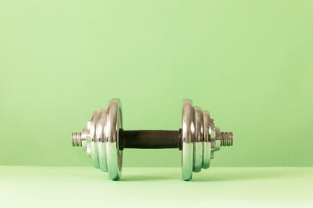 Large metal heavy dumbbell with pancakes on a green background with copy space. Fitness or bodybuilding concept background.