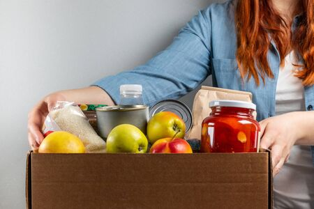 Woman hands hold food donation box with fruits, cereals, water and canned food.