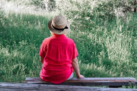 Blond woman in a hat with her back sits on a wood bench in park in the summer