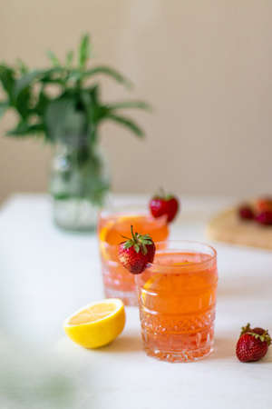 Two glass with strawberry lemonade or cocktail on a white background. Summer drinks with ice