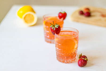 Lemonade with strawberries in glass on white background. Summer drinks with ice