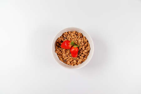 Top view breakfast bowls with granola, milk and organic tasty strawberries in a white bowl on white background. horizontal space for text Standard-Bild