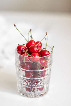 Close up of glass bowl with ripe cherries stands on a white background , vertical photo