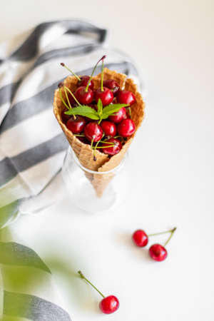 Fresh cherries in waffle cones Ice on white background. Healthy food. Summer creative concept