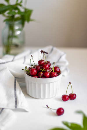 Fresh cherry in a ceramic bowl on white table. View from above. Vertical photo Standard-Bild