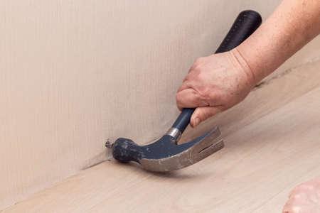 Closeup hand with nail and hammer at wall against light gray wall