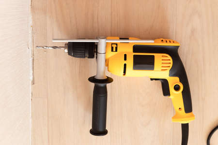 Drilling a hole in the wall with drill. Repair and construction in the house
