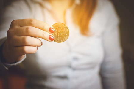 Woman holding in hand symbol of crypto currency Cryptocurrency golden bitcoin coin.