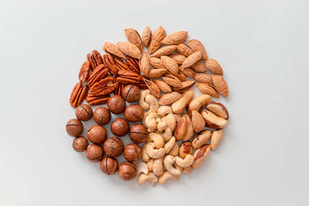 Circle background of nuts pecan, macadamia, walnut, almonds, hazelnuts on a white background. Top view, flat lay