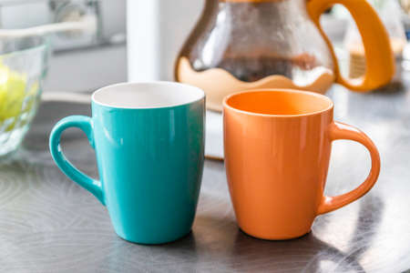 Two ceramic cups with a hot drink on the table on the kitchen