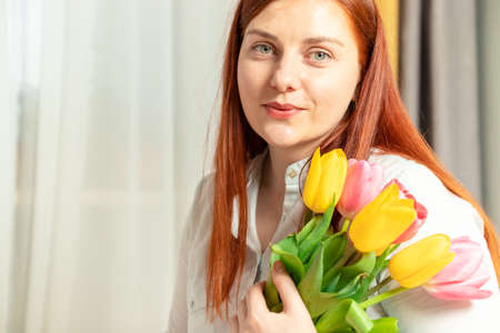 Beautiful red-haired girl in blue cotton blouse with fresh tulips bouquet in her hands on a gray wall background. Womens Day March 8. Valentines day, birthday concept