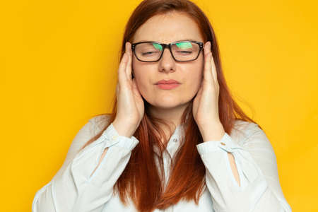 Depression unhappy woman in shirt and eyesight glasses with headache on yellow wall background. Stress, fatigue people concept. Hold hands on head Standard-Bild