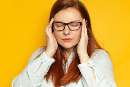 Depression unhappy woman with bipolar disorder clings to her head and experiences a headache.