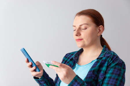 Beautiful young woman online shopping with credit card and smartphone sitting at home. Contactless payment concept
