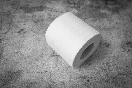 Roll of toilet paper on gray background. Diarrhea or constipation concept