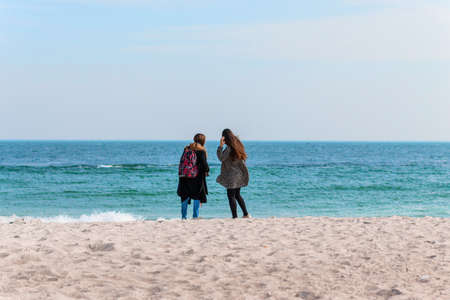 Young beautiful girlfriends stand with their backs on the beach and look at the sea
