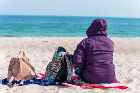 Lonely woman in a jacket and with a travel backpack sitting on the seashore and looking into the distance. Summer, travel concept Standard-Bild