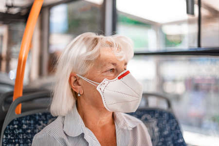 Caucasian blond woman in a protective mask sits in public transport at a distance of 2 m from other passengers. Protection and prevention covid 19, Coronavirus