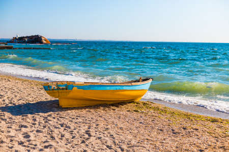 Beautiful seascape view with an old boat on the blue sea beach in sunny weather 免版税图像