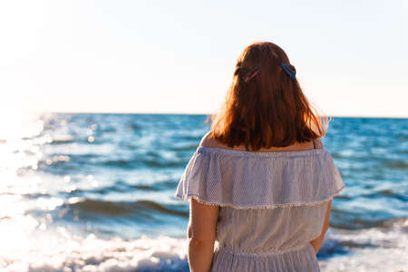 Young caucasian girl with her back stands on the beach near the sea and looks at the dawn