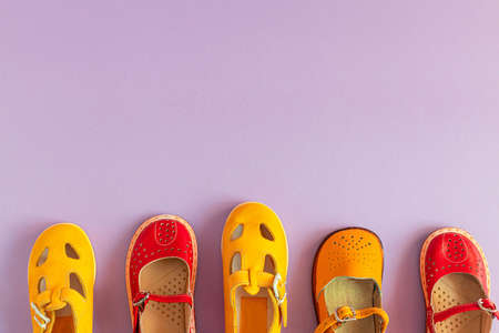 Stylish new yellow and red shoes on a colored pastel background with copyspace, top view, flat lay