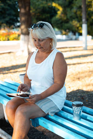 Freelancer blonde woman uses digital tablet device working in the park, outdoor. Imagens