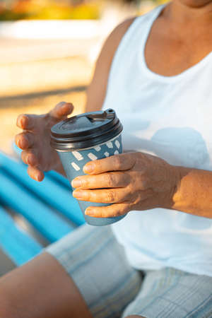 Woman hand with cup of takeaway coffee sitting on bench in green park on summer day,