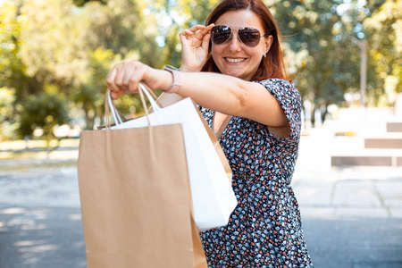 Beauty red smiling girl in sunglasses with shopping bags in the park on a sunny day. Shopping concept Imagens