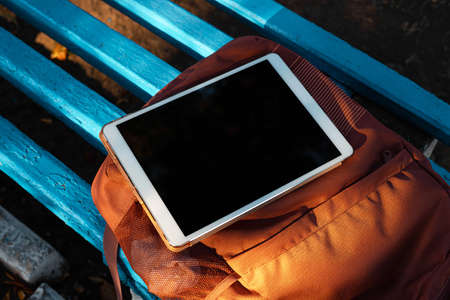Digital tablet on a backpack of a wooden bench.