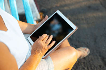 Close up of womans hand touching the digital tablet in the park outdoors.