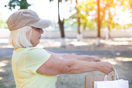 Female delivery courier holds paper bags with groceries to send to customer home. Commercial delivery concept Imagens