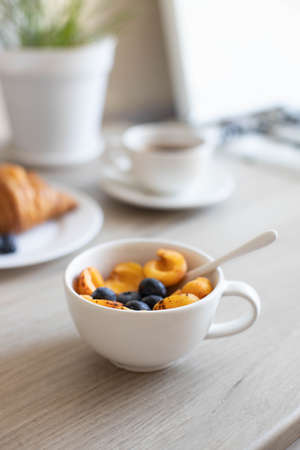 Delicious milk oatmeal or muesli with apricots and blueberries in a white bowl on a wooden table in the kitchen Imagens