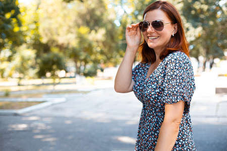 Cute red haired girl in sunglasses smiling and looking at the camera in the park