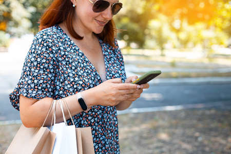 Happy red haired woman shopping online with mobile phone in the park on a sunny day. Shopping concept