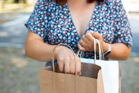 Woman hand holding paper shopping bag in the park on a sunny day. Shopping concept.