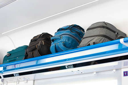 Carry-on luggage on the top shelf of the luggage compartment of an aircraft, train. Travel concept with copy space