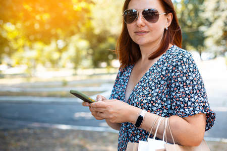 Woman using smartphone with shopping bags in hands in a park on a sunny day. Shopping concept