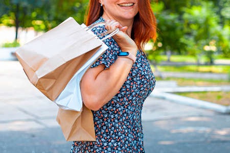 Portrait of a smiling woman carrying shopping bags in the park on a sunny day. Shopping concept