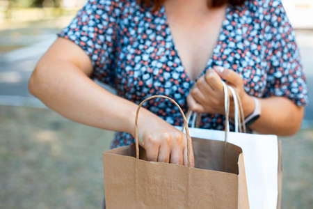 Woman hand holding paper shopping bag in the park on a sunny day. Delivery service concept.