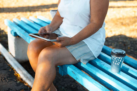 Freelancer blonde business woman using tablet in the park outdoors.