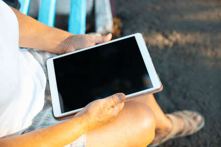 Close up of womans hand woman uses digital tablet devicet in the park outdoors.
