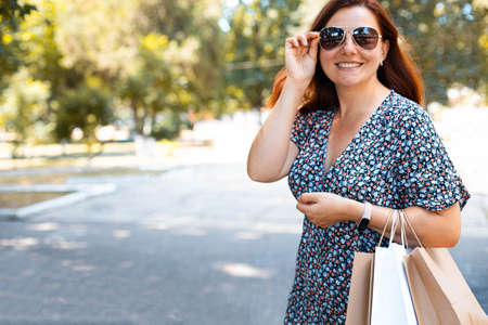 Happy beauty red smiling girl in sunglasses with shopping bags in the park on a sunny day. Shopping concept