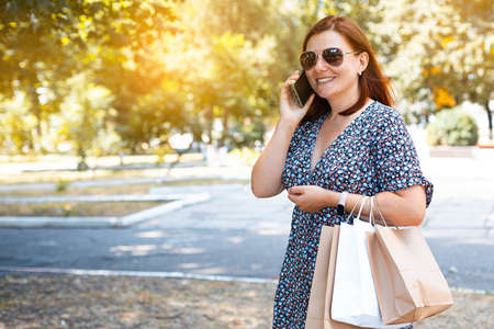 Happy beautiful red-haired smiling girl in sunglasses with shopping bags talking on a smartphone in a park on a sunny day. Shopping concept