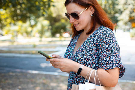 Woman using smartphone with shopping bags in hands in the park on a sunny day. Shopping concept