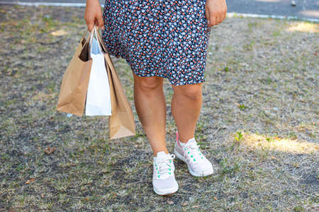 Female hand holding paper shopping bags in the park on the street. Clearance shopping concept