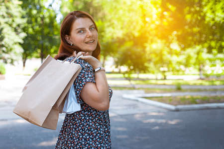 Beauty smiling girl in sunglasses with shopping bags in the park on a sunny day. Shopping concept